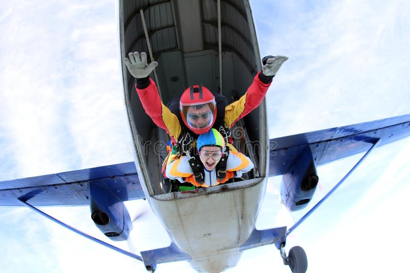 Tandem skydiving. Active woman are jumping out of a plane. stock photo