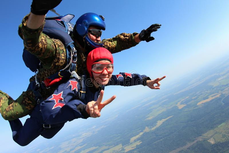 Skydiving tandem is falling in the blue sky. royalty free stock photo