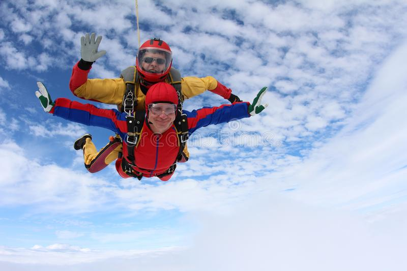 Tandem skydiving. Happy skydivers are in the amazing sky. stock photos