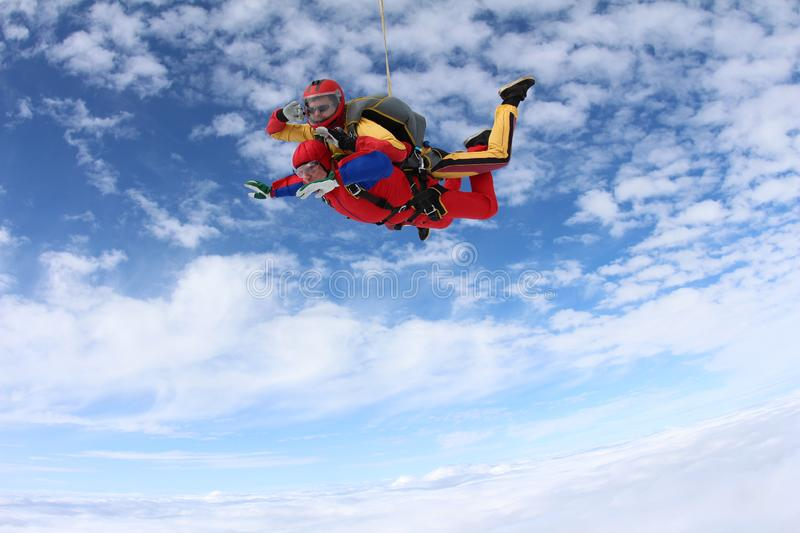 Tandem skydiving. Happy skydivers are in the amazing sky. stock images