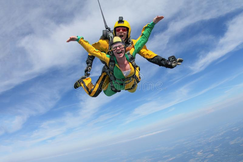 Tandem skydiving. A active girl is flying in the blue sky stock photos