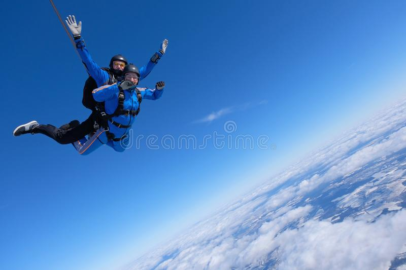 Tandem skydiving. Two guys are in the blue sky. royalty free stock photography
