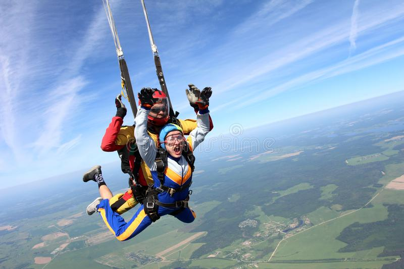 Tandem skydiving. Woman and instructor are in the sky. royalty free stock image