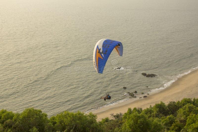 Tandemgleitschirme auf einem blauen Fallschirm fliegt über grüne Bäume gegen einen sandigen Strand und einen Ozean stockfoto