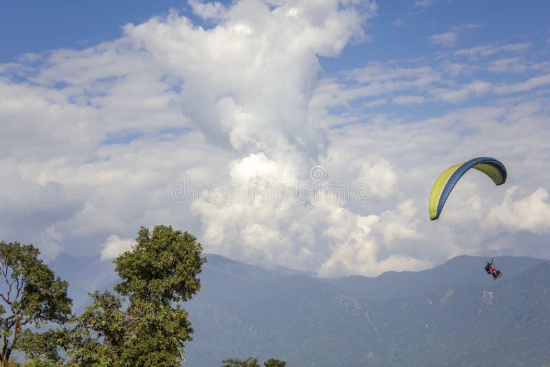 Tandemgleitschirme im Himmel gegen den Hintergrund eines nebelhafter Gebirgstales und der schweren weißen Wolken lizenzfreie stockbilder