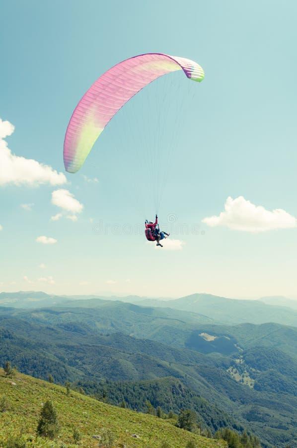 Tandemgleitschirmfliegenflug mit Hügeln und blauem Himmel lizenzfreies stockbild