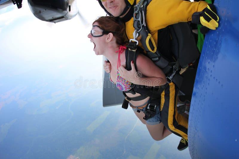 Tandemowy skydiving Wyjście Dziewczyna jest krzycząca obraz stock