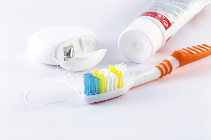 Tandenborstel, tandzijde en tandpasta op witte achtergrond stock afbeelding