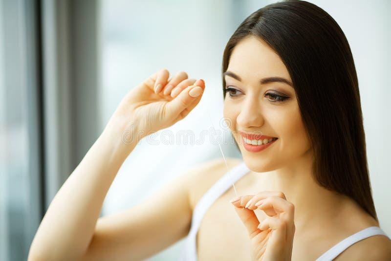 Tandenzorg De mooie het Glimlachen Gezonde Witte Tanden van Vrouwenflossing stock fotografie