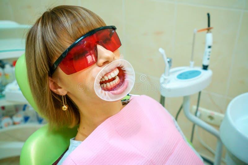 Tandheelkunde gelukkige patiënt als voorzitter in beschermende brillen royalty-vrije stock foto