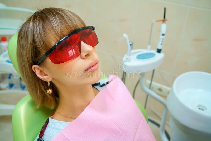 Tandheelkunde gelukkige patiënt als voorzitter in beschermende brillen stock fotografie