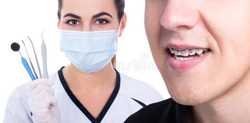 Tandläkare eller orthodontist och ung man med hänglsen på tänder fotografering för bildbyråer