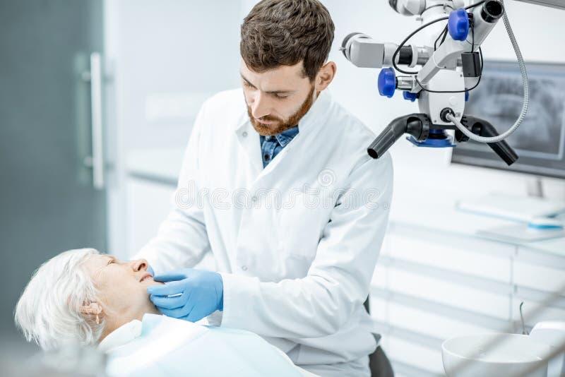 Tandläkare med den höga kvinnapatienten i det tand- kontoret för kirurgi arkivbilder