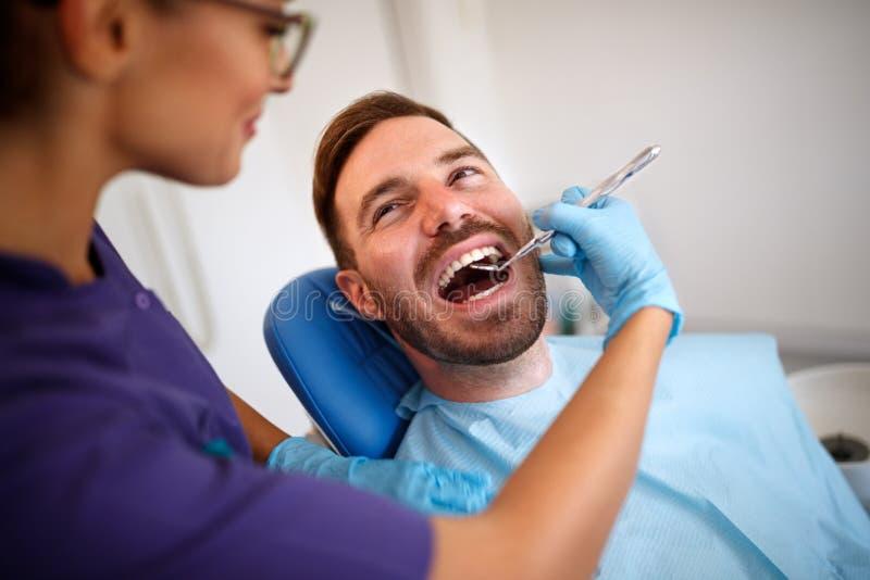 Tandläkare med den tand- spegeln som kontrollerar upp patient'ständer royaltyfri foto