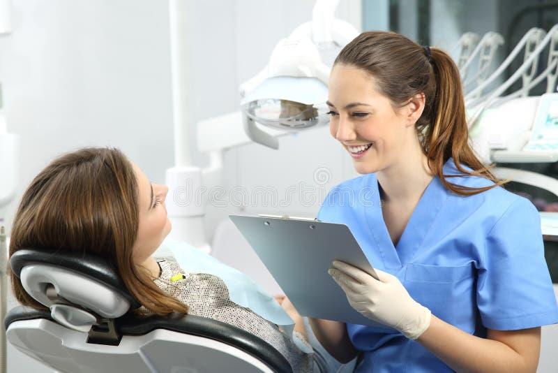 Tandläkare med medicinsk historia som frågar till en patient arkivfoton