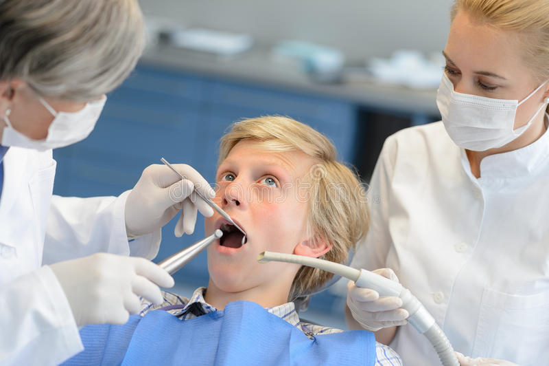 Tandläkare och assistent med den förskräckta tonårs- patienten royaltyfria foton