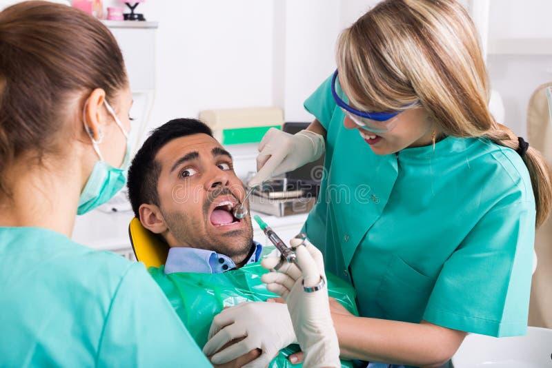 Tandläkare och förskräckt patient arkivbild