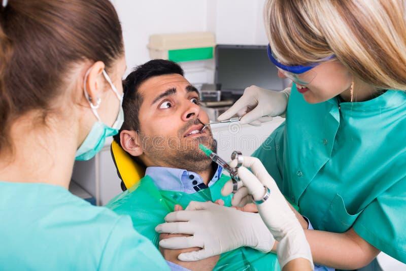 Tandläkare och förskräckt patient arkivbilder
