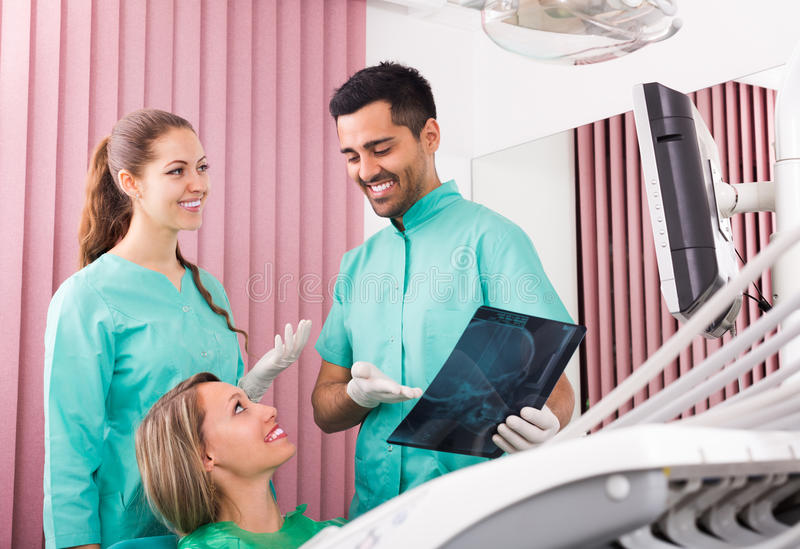 Tandläkare och klient som ser en röntgenstrålebild arkivbilder