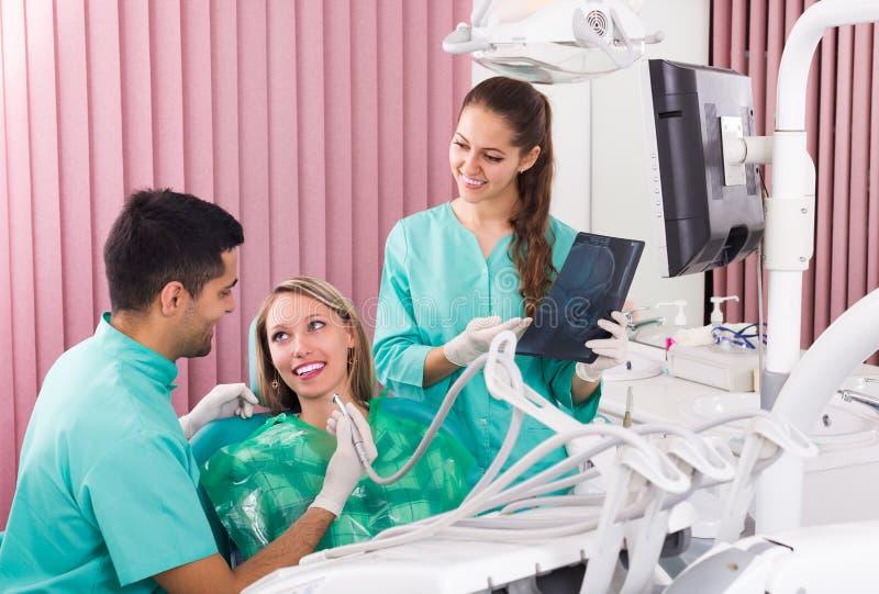 Tandläkare och klient som ser en röntgenstrålebild arkivbild