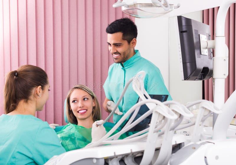 Tandläkare och klient som ser en röntgenstrålebild royaltyfri fotografi