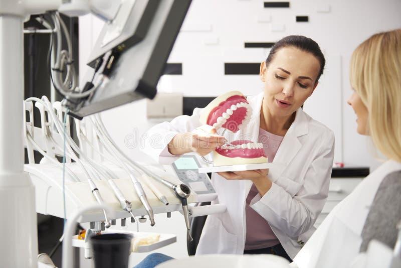 Tandl?kare och kvinna som har en konversation i tandl?kares klinik arkivfoto