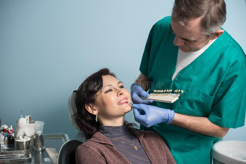 Tandläkare- och kvinnligpatient som kontrollerar och väljer färg av tänderna i tand- klinikkontor dentistry royaltyfria foton