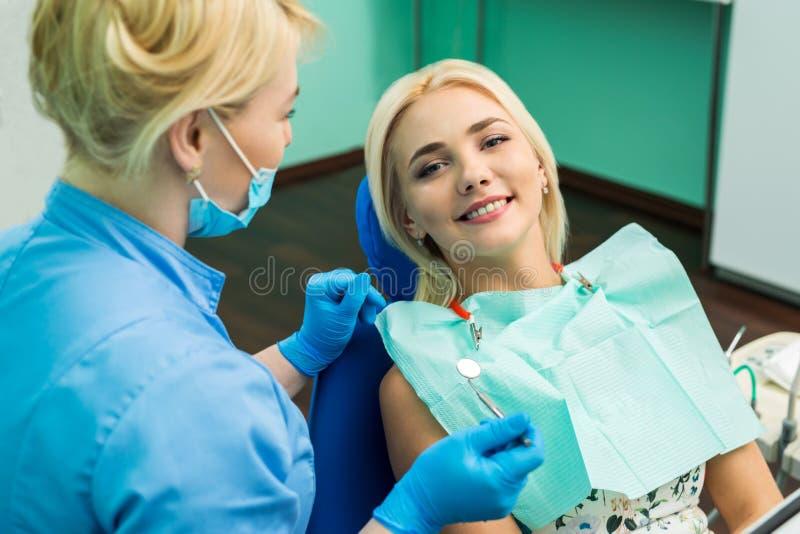 Tandläkare och lycklig le blond kvinna Arbete av stomatologisten med patienten Gör ditt leende perfekt royaltyfri foto