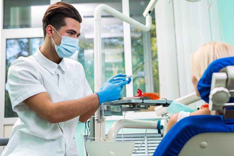 Tandläkare och lycklig le blond kvinna Arbete av stomatologisten med patienten Gör ditt leende perfekt arkivbild