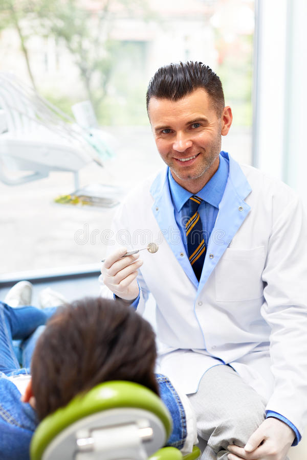 Tandläkare och patient i tandläkarekontor Ung man i det tand- cet royaltyfria foton