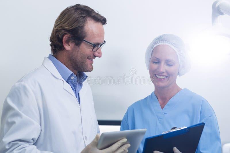 Tandläkare och tand- assistent som arbetar på den digitala minnestavlan royaltyfria bilder