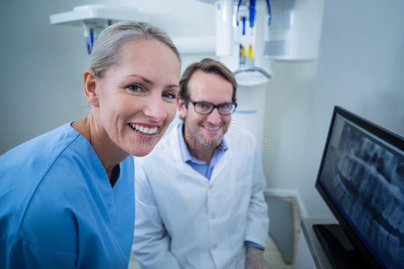 Tandläkare och tand- assistent som diskuterar en röntgenstråle på bildskärmen fotografering för bildbyråer