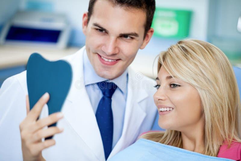 Tandläkare och tillfredsställd tålmodig med vita tänder arkivfoton