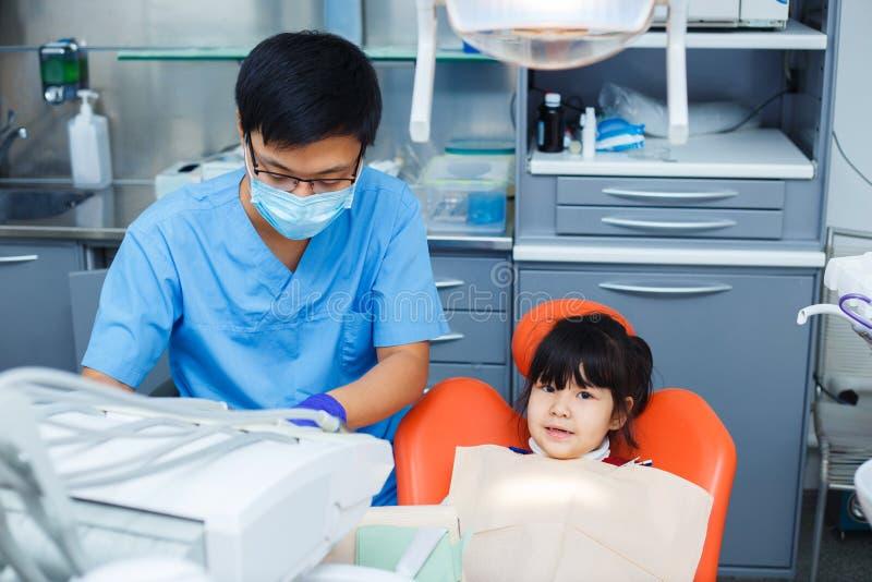 Tandläkare på arbete och hans lilla unga gladlynta patient Asiat doc arkivfoto