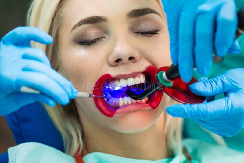 Tandläkare räcker arbete på patient för ung kvinna med tand- hjälpmedel Kvinnlig patient med retractoren på tandläkaren royaltyfri bild