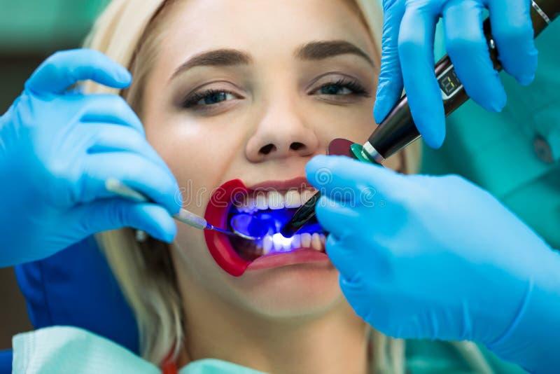 Tandläkare räcker arbete på patient för ung kvinna med tand- hjälpmedel Kvinnlig patient med retractoren på tandläkaren royaltyfria foton