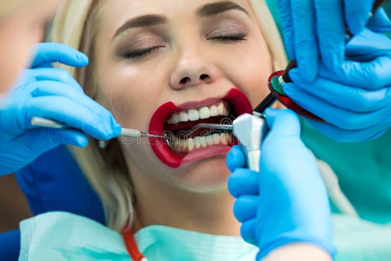 Tandläkare räcker arbete på patient för ung kvinna med tand- hjälpmedel Kvinnlig patient med retractoren på tandläkaren royaltyfri foto