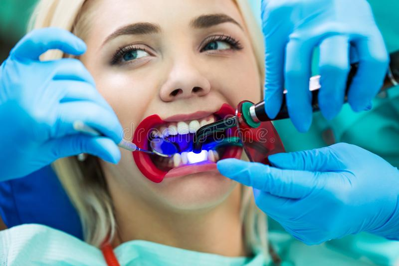 Tandläkare räcker arbete på patient för ung kvinna med tand- hjälpmedel Kvinnlig patient med retractoren på tandläkaren arkivfoton