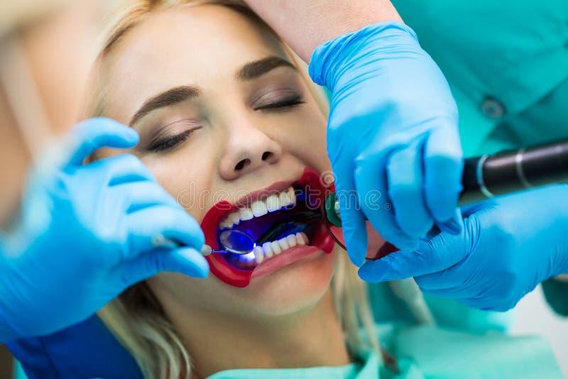 Tandläkare räcker arbete på patient för ung kvinna med tand- hjälpmedel Kvinnlig patient med retractoren på tandläkaren fotografering för bildbyråer