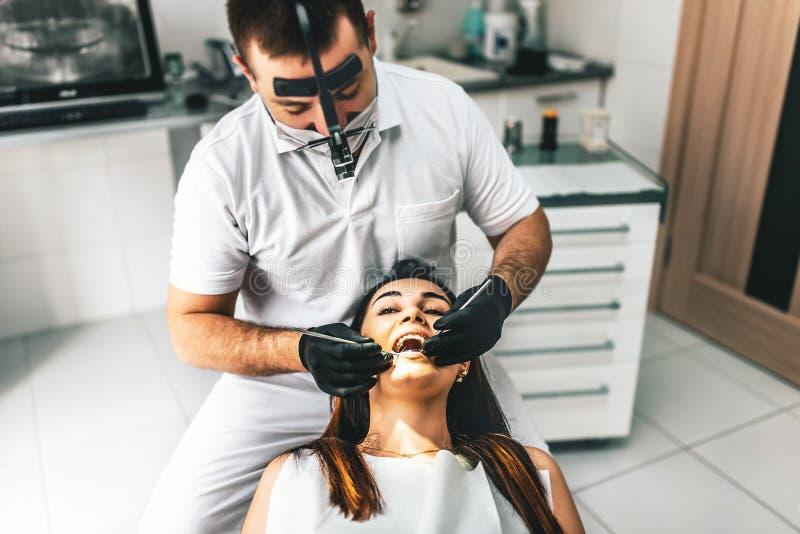 Tandläkare som arbetar i tand- klinik med den kvinnliga patienten i chaien royaltyfri bild