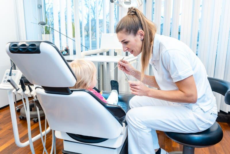 Tandläkare som behandlar ett barn på sitt kontor royaltyfri fotografi