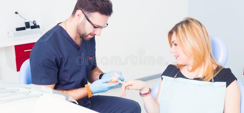 Tandläkare som explaing tand- behandling med tandprotesen till den kvinnliga patienten royaltyfri foto