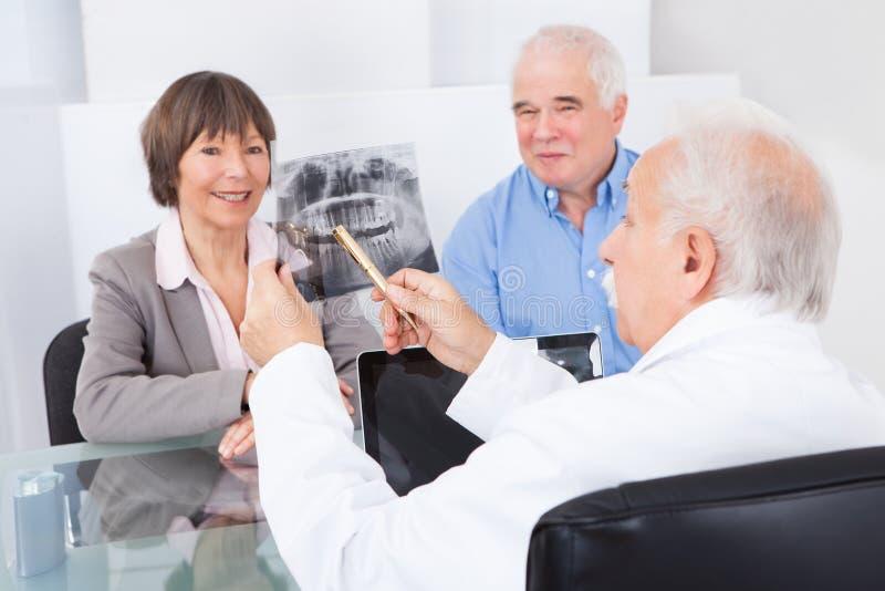 Tandläkare som förklarar röntgenstrålen till höga par arkivfoton