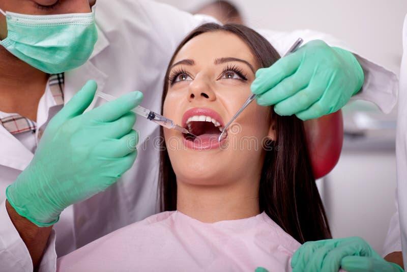 Tandläkare som ger anestesi till patienten royaltyfria bilder