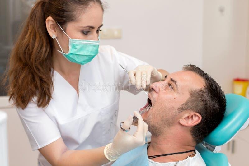 Tandläkare som ger en injektion av anestesi till patienten royaltyfria bilder