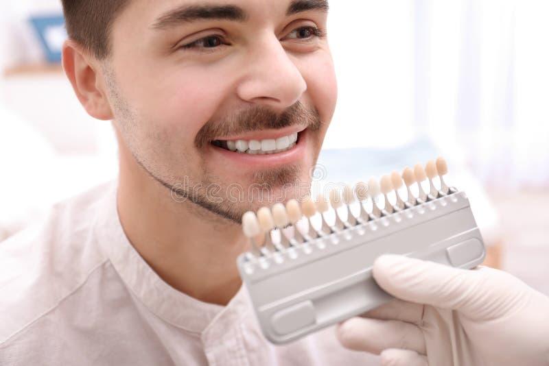 Tandläkare som kontrollerar ung mans tandfärg royaltyfri foto