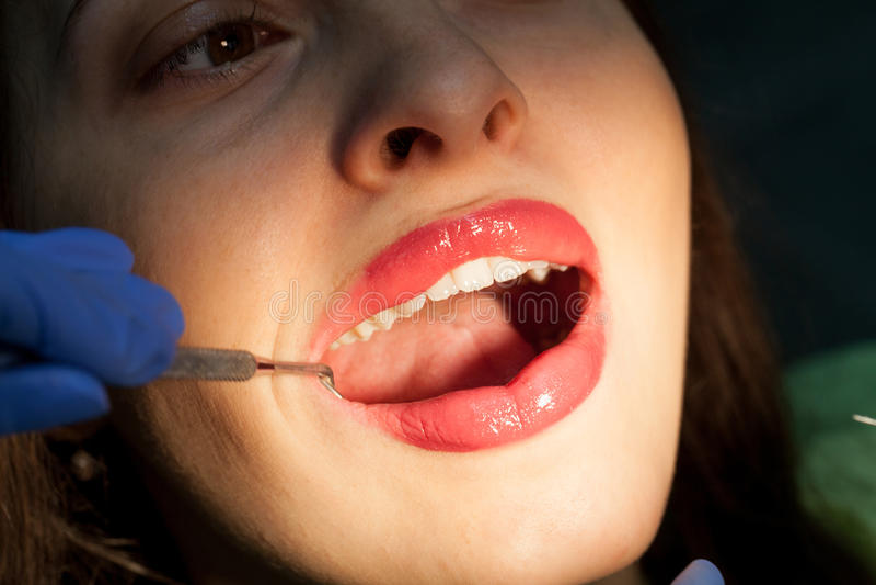Tandläkare som kurerar en kvinnlig patient arkivfoto
