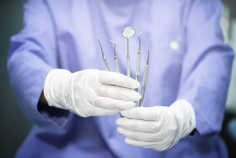 Tandläkare som rymmer tand- utrustning royaltyfri fotografi