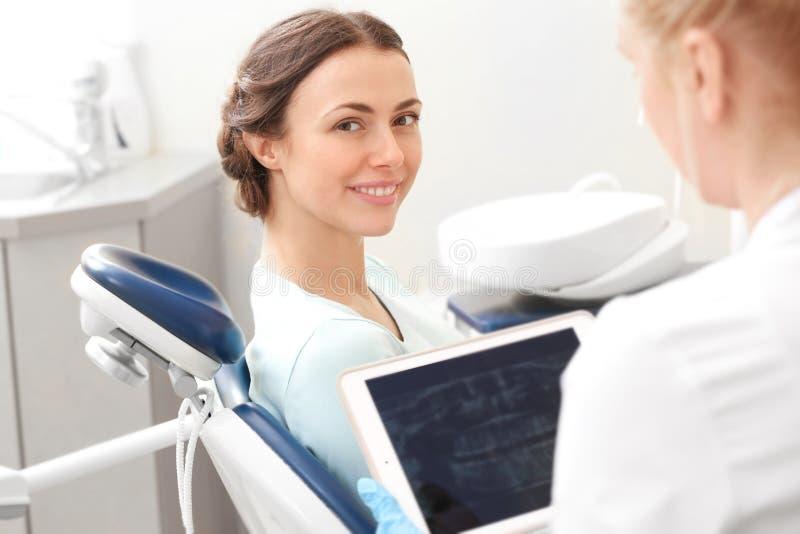 Tandläkare som ser röntgenstrålebild av tänder för ` s för y-oungkvinna arkivfoto