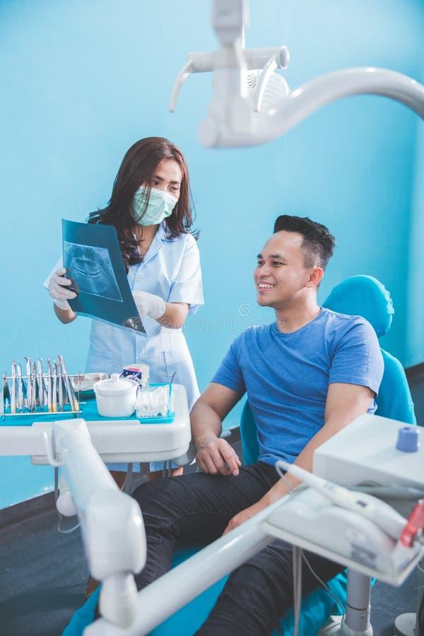 Tandläkare som talar med hennes tålmodiga förklarande x-stråle arkivfoton